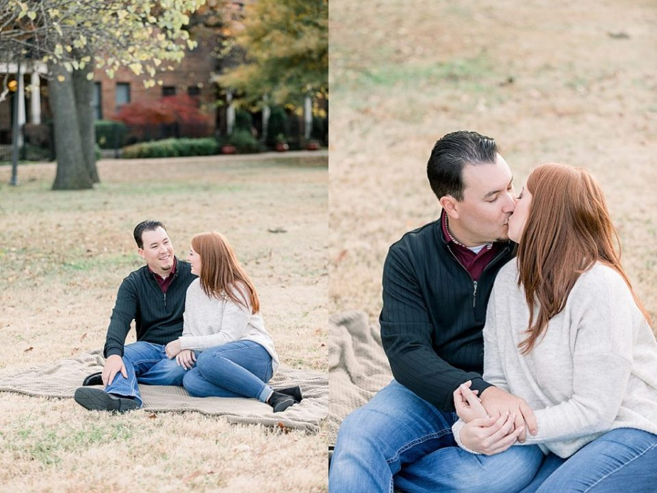 Couple cuddling and kissing on blanket at Tulsa Centennial Park engagement