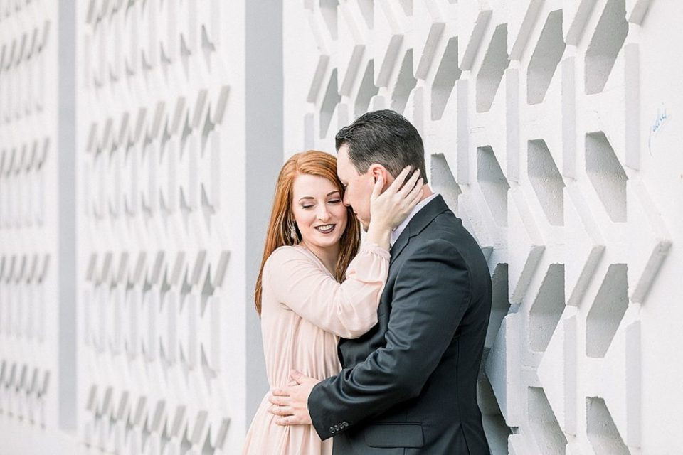 Couple cuddling against white brick wall