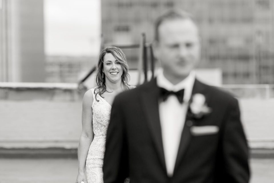 BW Bride walking up to groom on rooftop of Tulsa Club Hotel for first look