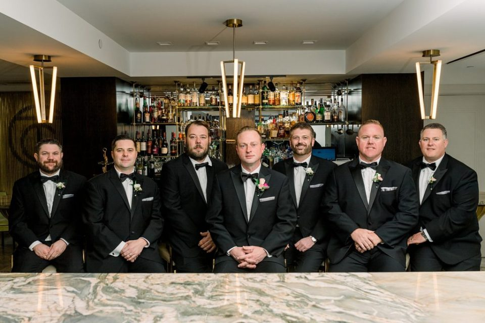 Groom and groomsmen standing at bar at Tulsa Club Hotel wedding