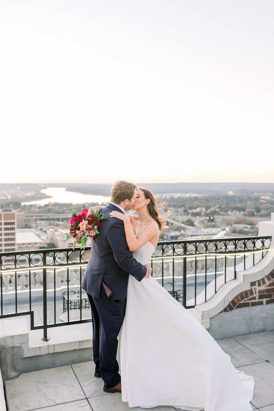 Bride and groom kiss on rooftop at The Mayo Hotel wedding