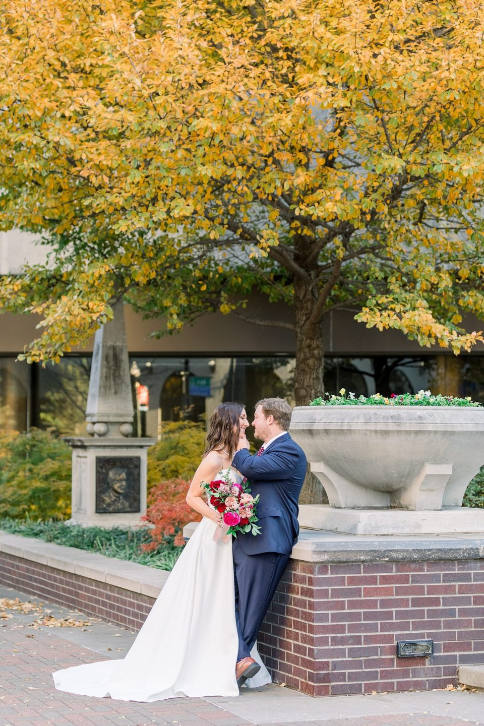 Bride and groom kiss under yellow tree in downtown Tulsa wedding