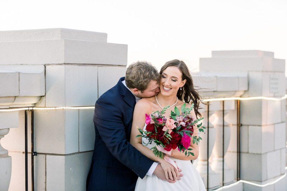 Groom kisses bride on neck on rooftop of the Mayo Hotel
