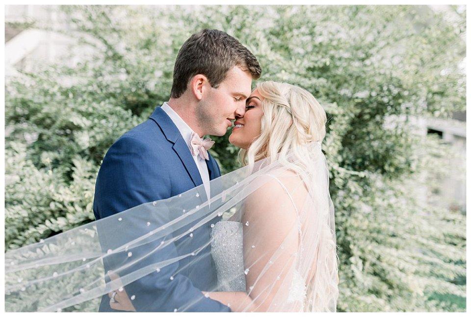 Bride and groom kiss under sweeping crystal veil