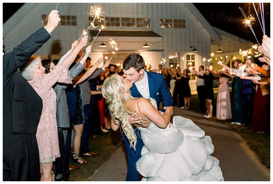 Groom dips bride for kiss during sparkler exit at Spain Ranch