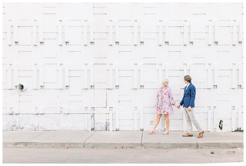 Couple holding hand walking in front of large white brick wall  in Guthrie Green / Centennial Park Tulsa engagement