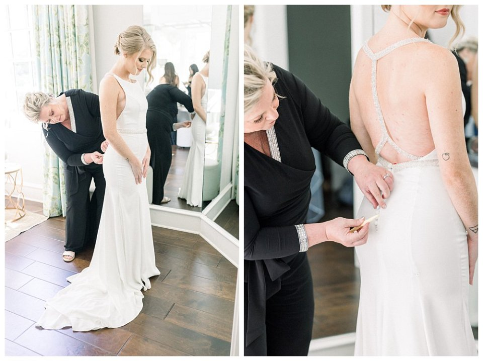 Bride being zipped into wedding gown