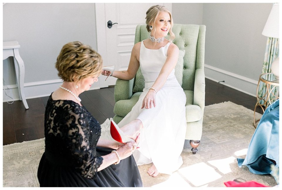 Mother of the bride putting louboutin wedding heels on bride