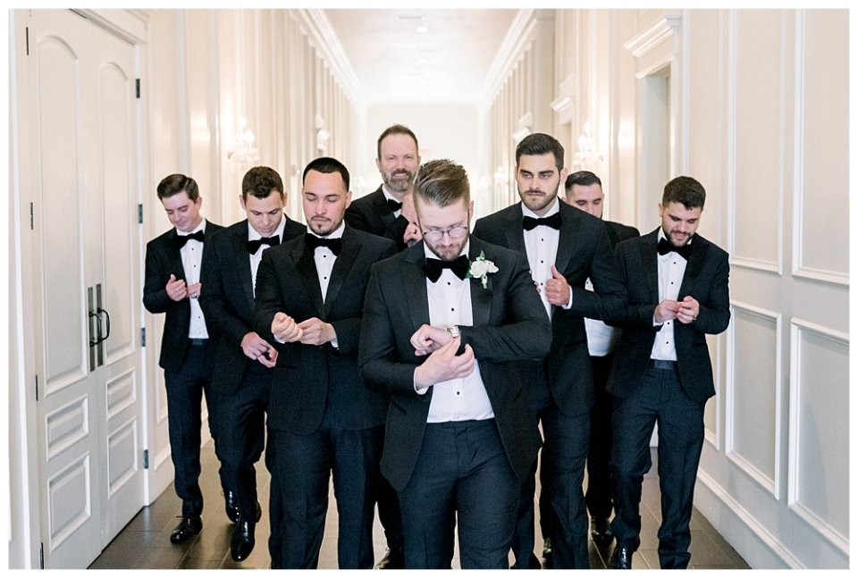 Groom walking down hall with groomsmen at The Milestone Mansion wedding in Aubrey TX