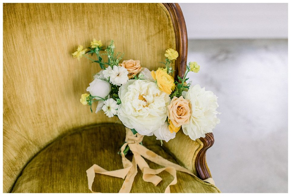 white and yellow bridal bouquet in vintage chair