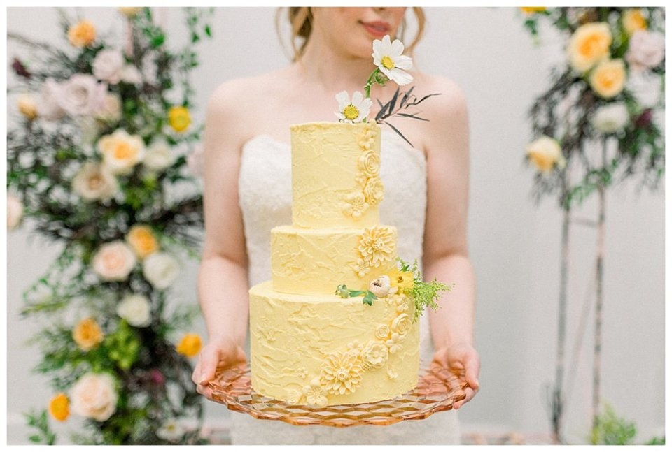 Bride holding 3 tiered yellow wedding cake
