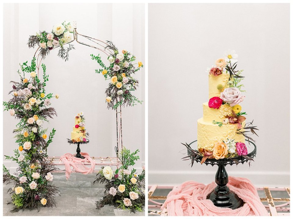 3 tiered yellow wedding cake under floral arch