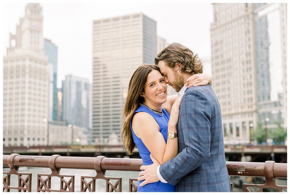 Couple embracing on bridge in Chicago engagement