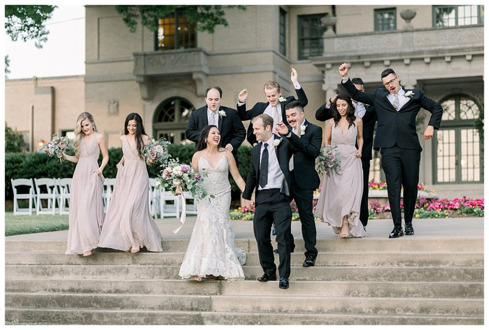 Wedding party celebrating walking down steps at Mansion at Woodward Park wedding