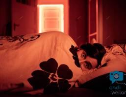 """Ein Mann liegt mit ängstlich im Bett. Im Hintergrund """"glüht"""" eine Tür"""