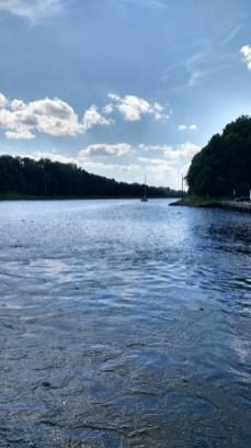 Blick auf einen Kanal mit einem Segelboot mit eingezogenen Segeln