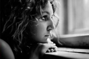 sad-woman-looking-out-dark-window-550x365