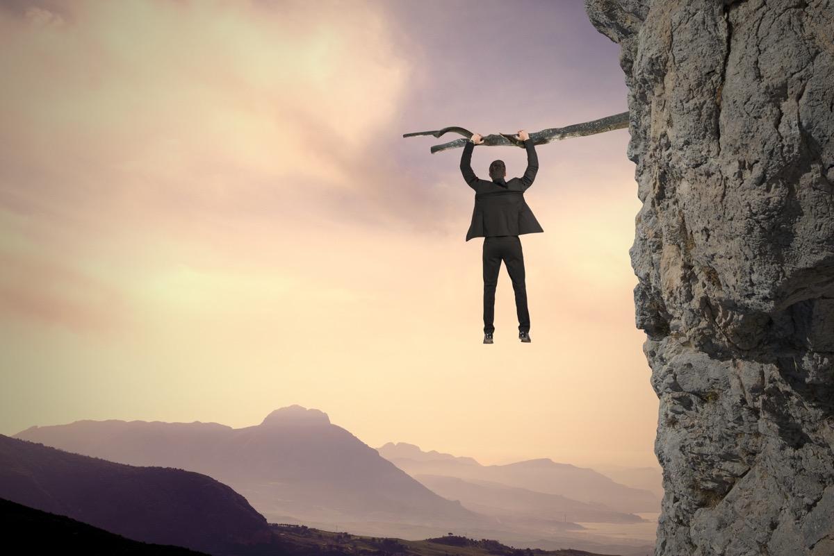 Unternehmer Risiko Mann hängt am Abgrund