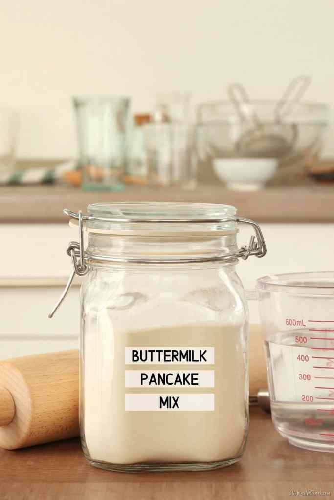 clear glass canning jar on counter in front of rolling pin and measuring cup. Jar is full of pancake mix. Label on jar says buttermilk pancake mix