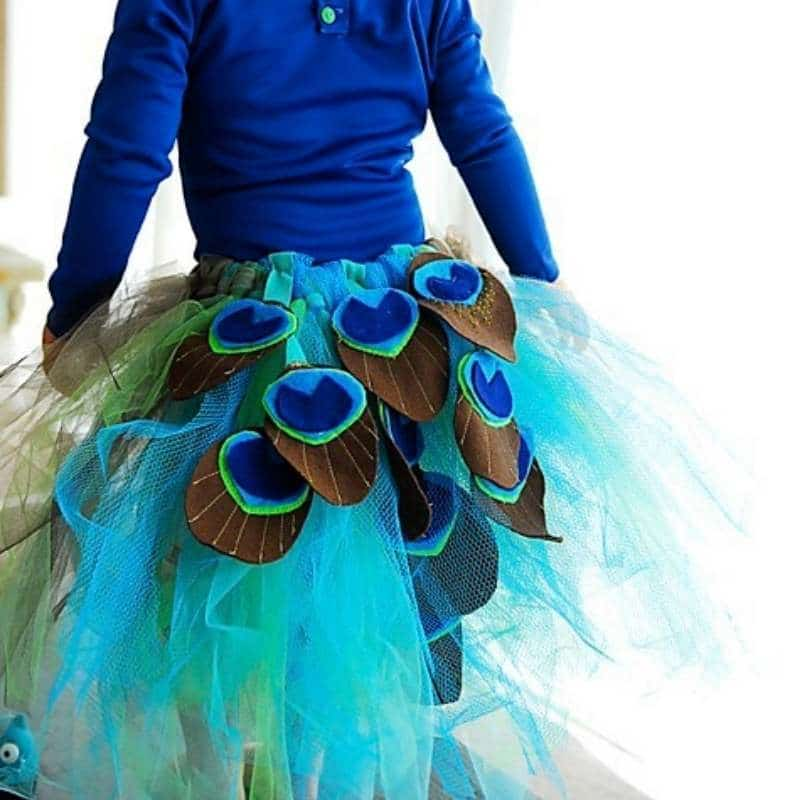 diy peacock tutu costume - green and turquoise tulle with felt peacock colored shapes sewn on back of tutu. Girl wearing tutu is wearing a peacock blue long sleeve shirt