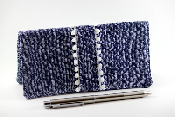 Checkbook cover with pom pom trim