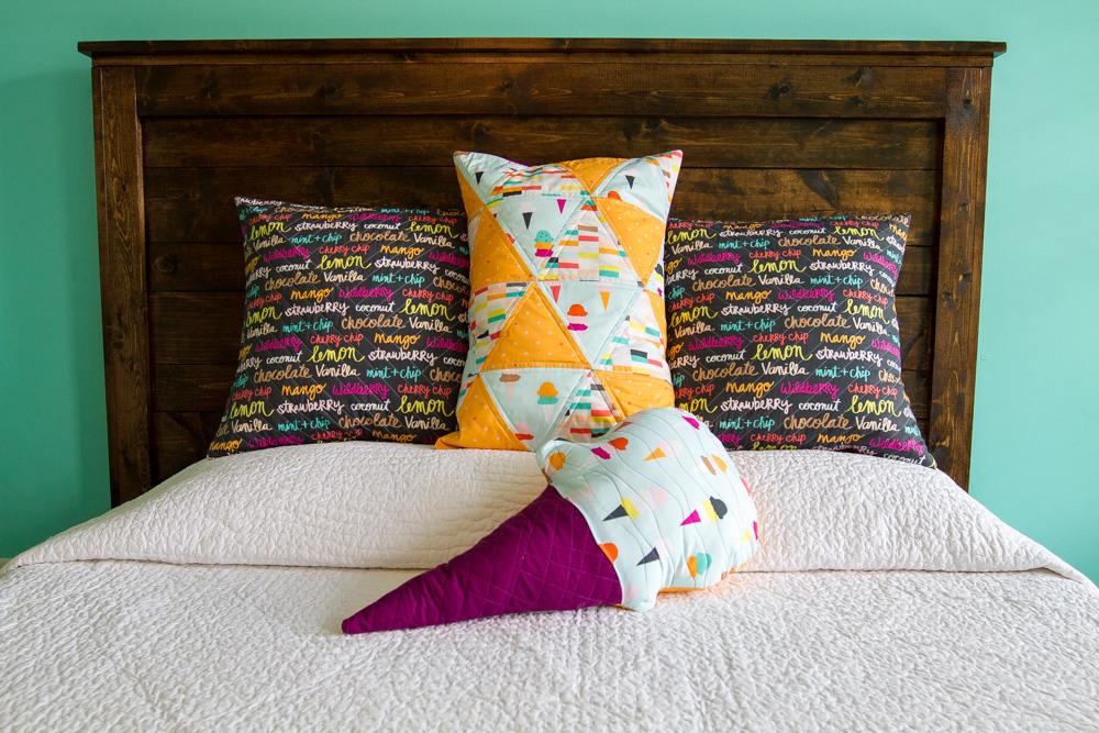 two square quilted pillows and one rectangular quilted pillow and one ice cream cone shaped pillow on bed with white cover