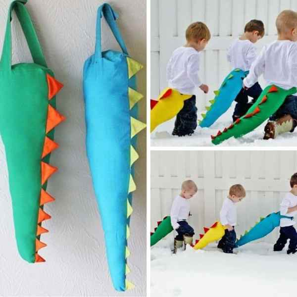 blue, green and yellow stuffed dinosaur tails worn by 3 little boys in snow