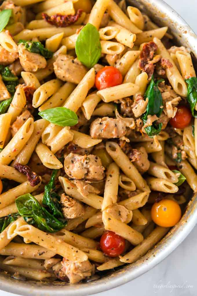 Pot full of diced chicken, penne pasta, spinach and small tomatoes in a cream sauce.