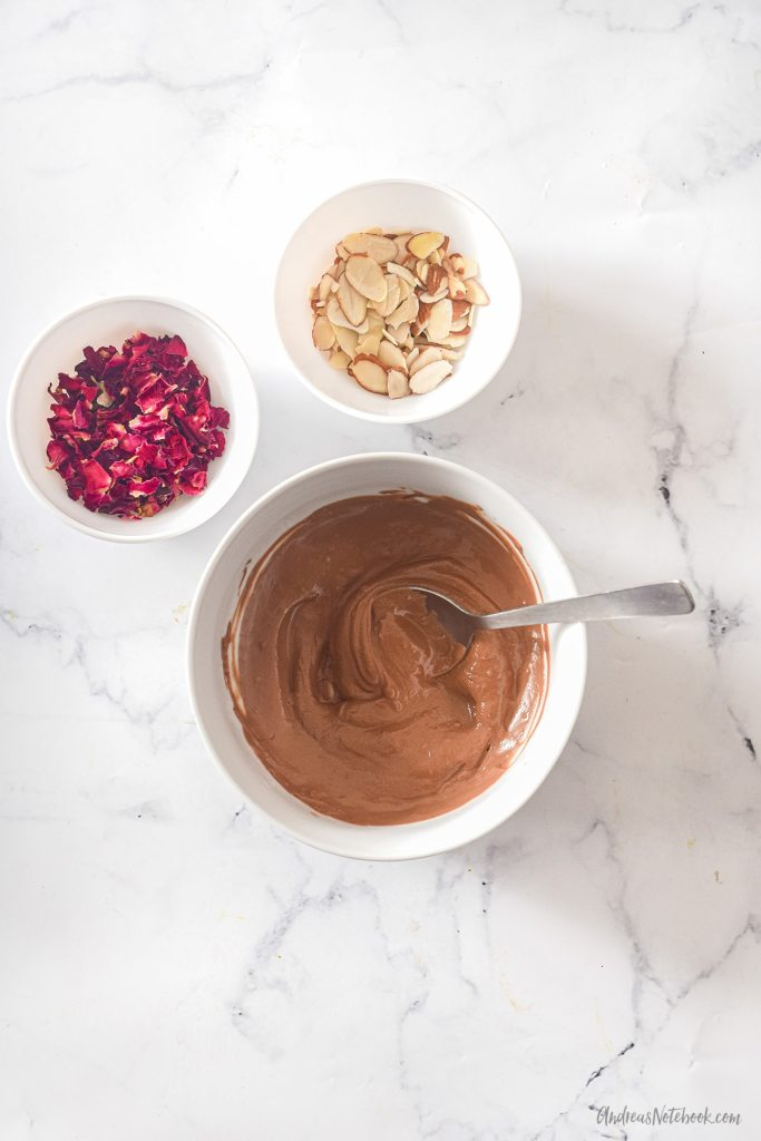 rose vanilla shortbread cookie frosting ingredients in bowls - melted chocolate, rose and almonds