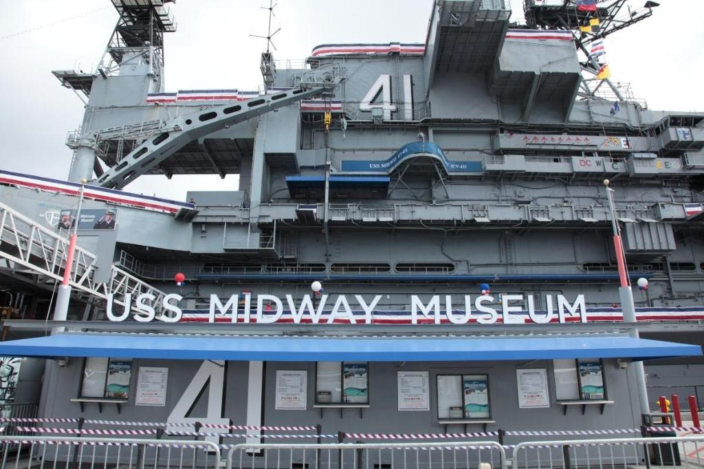 USS Midway Museum entrace with 4 ticket windows in front of the giant aircraft carrier