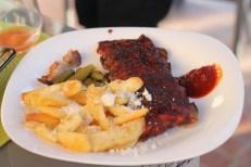 Coaste de porc la grătar cu cartofi la cuptor cu parmezan, sos barbecue și castraveți