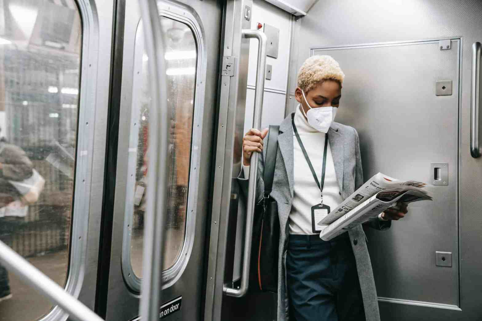 focused woman in mask, due to COVID-19 pandemic, reading newspaper in metro train