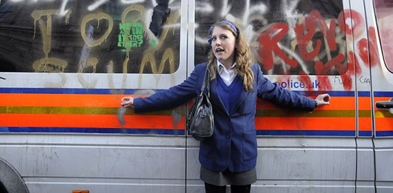 PROTECTIVE_Zoe Williams protects a police riot van covered in graffiti