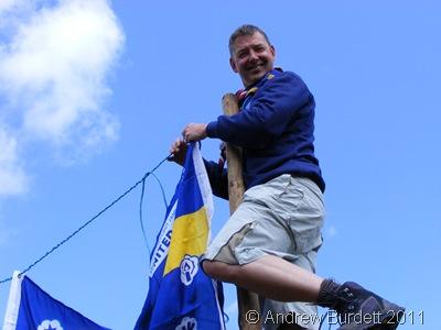 MAN UP_Jim Payen hanging a Jamboree UK Contingent flag on the gateway.