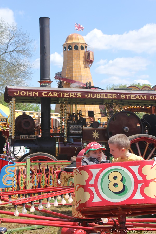 MILDLY TERRIFIED: Children enjoy one of the younger rides in front of the Verity steam engine and helter-skelter. (IMG_2665)