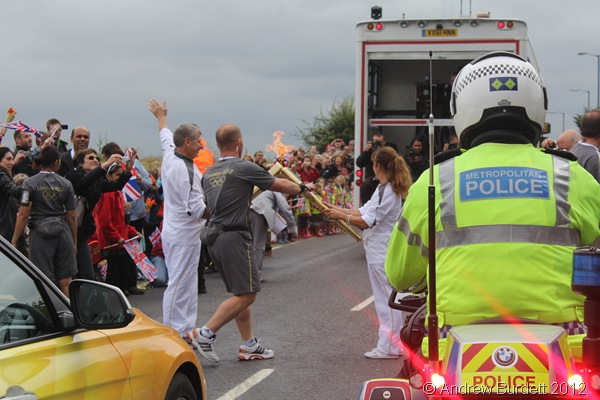 PASS IT ALONG: As one torchbearer's short run came to an end, another's began. (IMG_8785_ARB)
