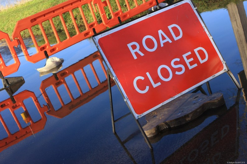 Temporary signs and fencing prevented cars from driving down the flooded lower road.