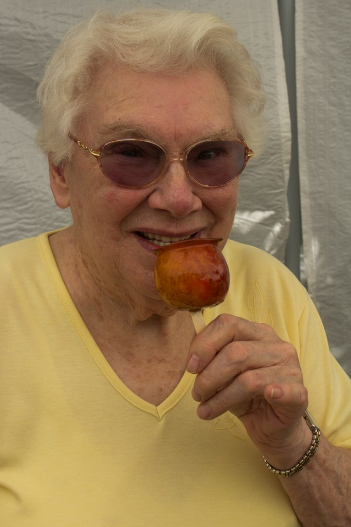 Phyllis Sigsworth takes a bite out of a toffee apple.