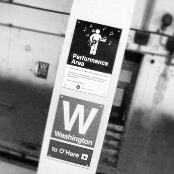 Performance area at Washington Subway Station, Chicago. Black and white photo of a post with signs