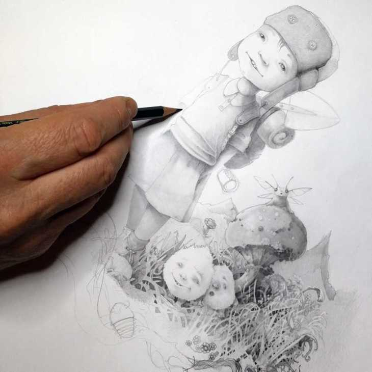 Hand with pencil drawing a little boy and small fluffy creatures