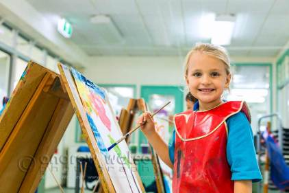Image of young student with paint and easel