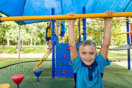Young school boy climbing on playground equipment