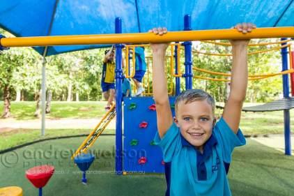 Young school boy climbing on playground equipment