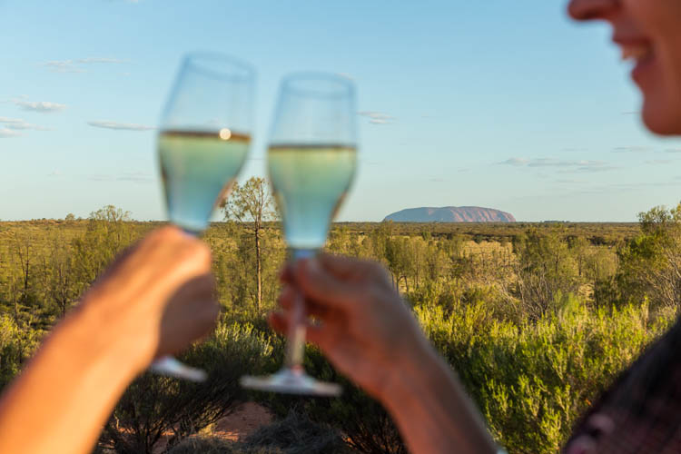 Image of guests enjoying a sunset drink with Uluru in the distance