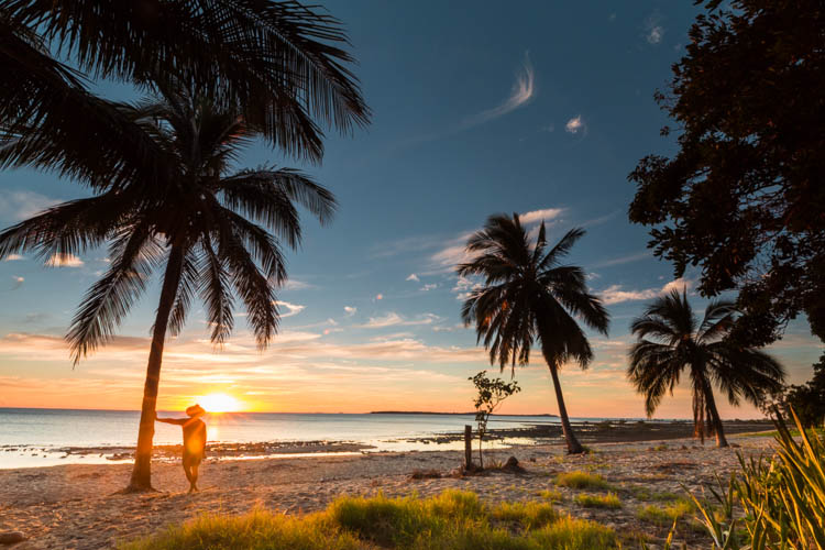 Image of visitor standing amidst coconut palms at Clairview Beach