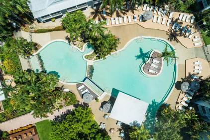 Aerial view of resort pool surrounded by sun lounges and umbrellas