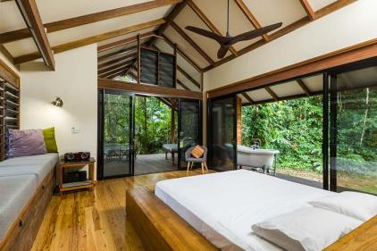 Bedroom interior with outdoor deck and bathtub at a Daintree holiday home