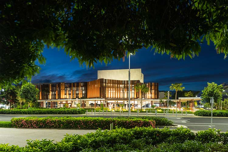 View through foliage to the Cairns Performing Arts Centre at twilight