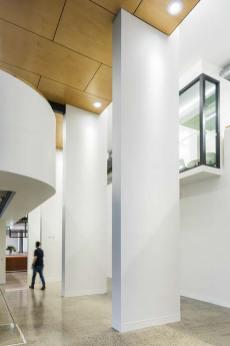 A man walking through high-ceiling gallery space