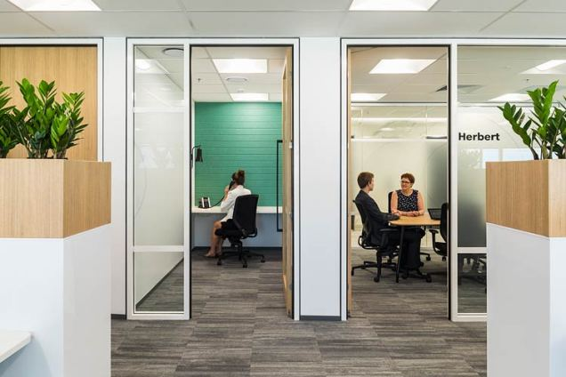 Looking through office doors to staff members having meetings